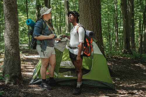 Male friends with backpacks near tent in woods
