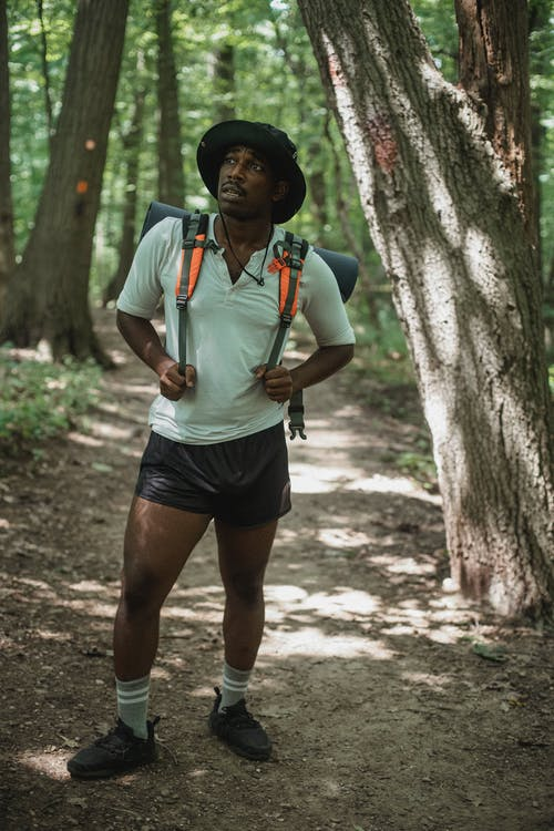 Young contemplative African American tourist looking up on path in summer forest during trip