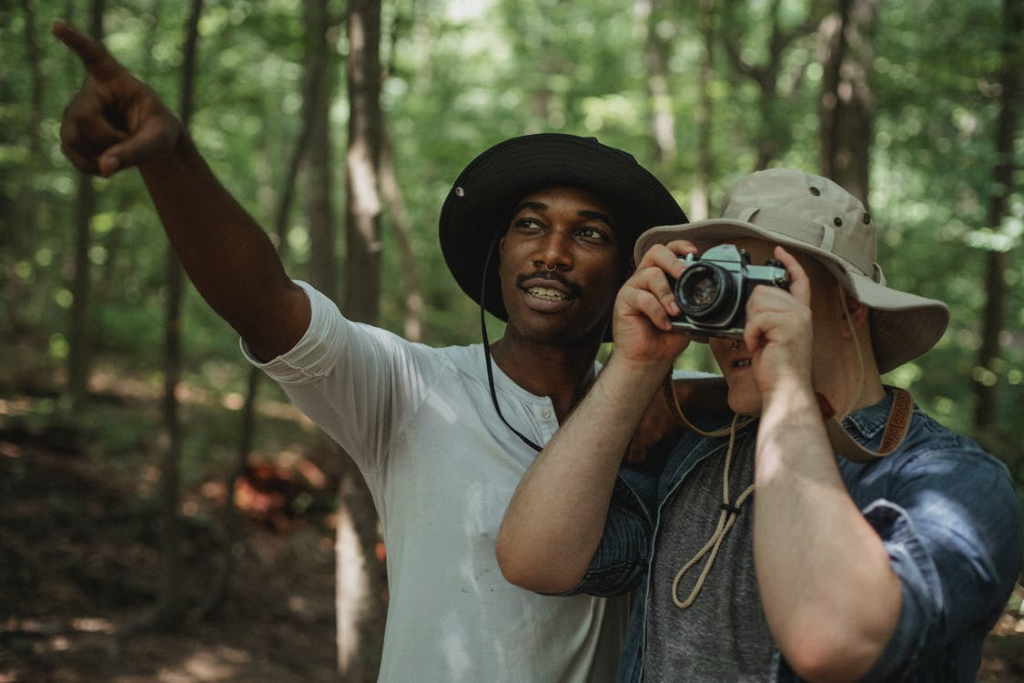 Young black male traveler indicating with finger near anonymous best friend taking photo on camera in woods