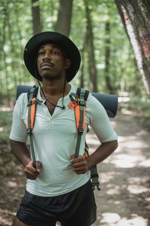 Young emotionless ethnic male tourist with rucksack and piercing looking forward on pathway in woods