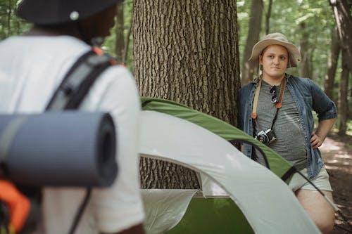 Viajante Com Câmera Fotográfica Perto De Um Parceiro Negro Irreconhecível Na Floresta