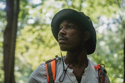 Concentrated young African American male backpacker in casual clothes and safari hat standing in green forest and looking away attentively