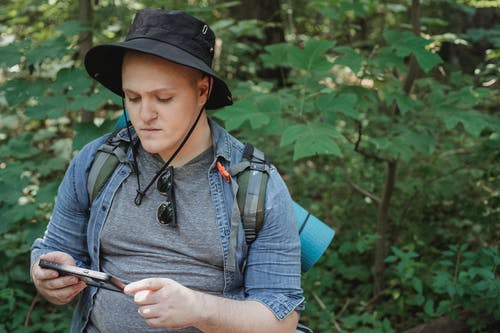 Serious young man using tablet in forest during hiking tour