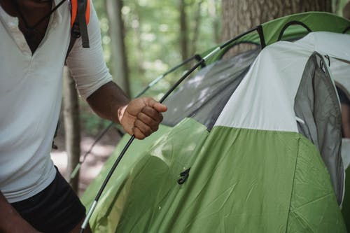 Crop unrecognizable African American male traveler in casual clothes setting up tent near tree in forest while preparing for camping