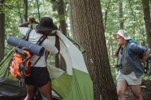 Traveling men in shorts and hats setting up camping tent in woods