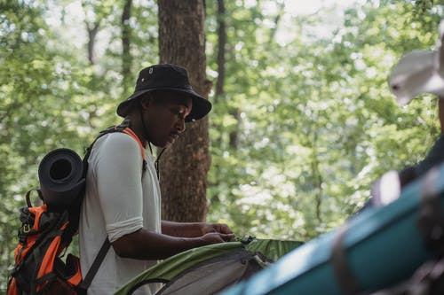 Concentrating young black guy setting up camping tent in woods