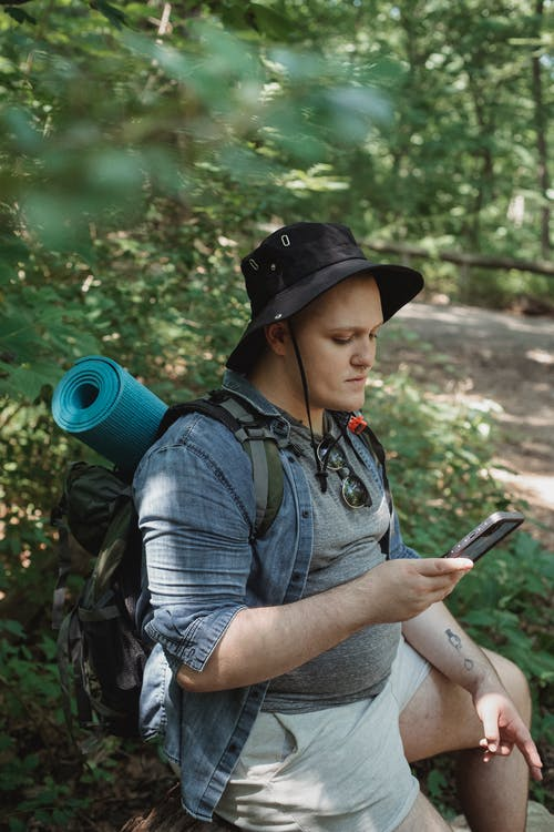 Young plump tourist with hiking equipment browsing internet on cellphone in green forest near walkway
