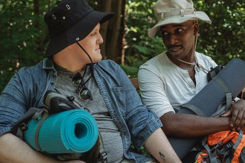 Crop diverse friends with hiking equipment talking in forest