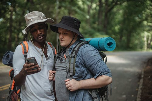 Multiracial male hikers sharing smartphone on countryside road