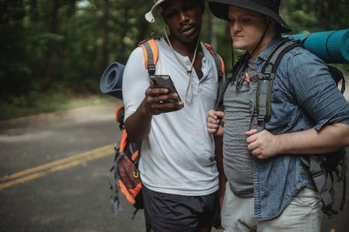 Crop diverse tourists with rucksacks watching smartphone on road