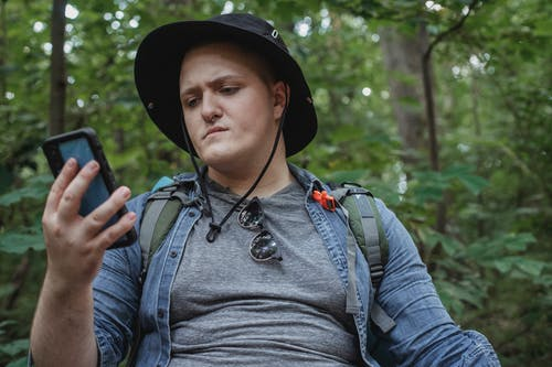 Young concentrated traveler in panama hat surfing internet on cellphone against green woods during hike