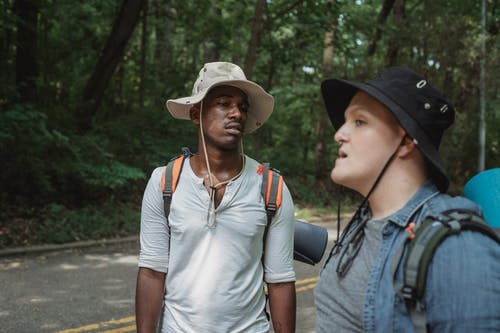 Diverse male travelers with rucksacks conversing on roadway