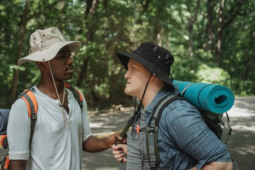 Young multiracial backpackers in panama hats speaking on roadway against woods while looking at each other