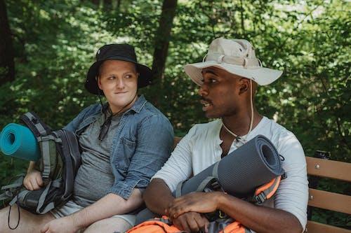 Multiethnic backpackers speaking on bench in woods
