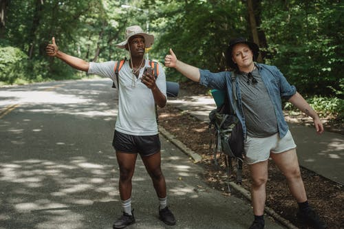 Young multiethnic tourists with backpacks standing with smartphone while showing like gesture on roadway near forest and looking away