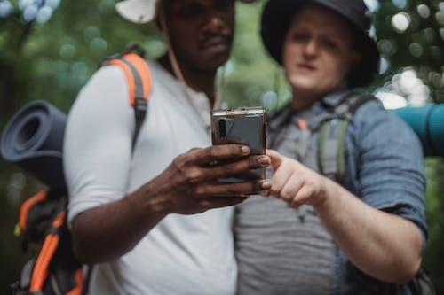 Crop multiethnic travelers sharing smartphone during summer trip