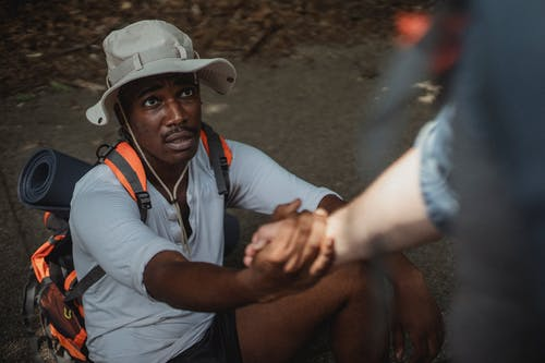 Black male hiker holding hand of anonymous homosexual partner