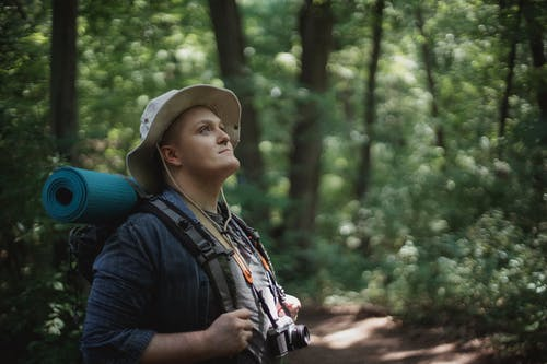 Dreamy male tourist with hiking equipment exploring green forest