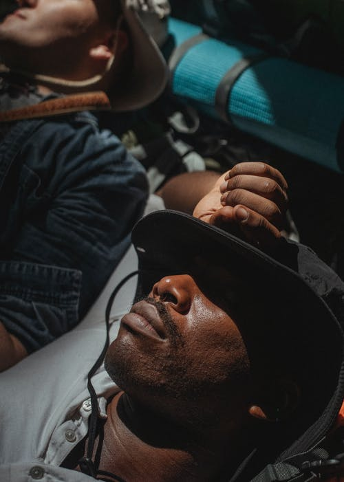 From above multiracial men covering eyes with hats and sleeping in camp tent after intense trekking