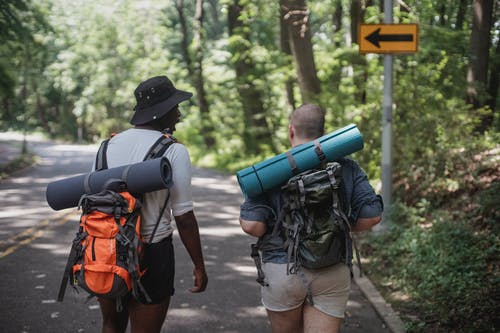 Unrecognizable diverse male hikers with backpacks walking along road
