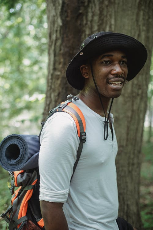 Side view content African American male traveler with trekking equipment and backpack standing in green woods