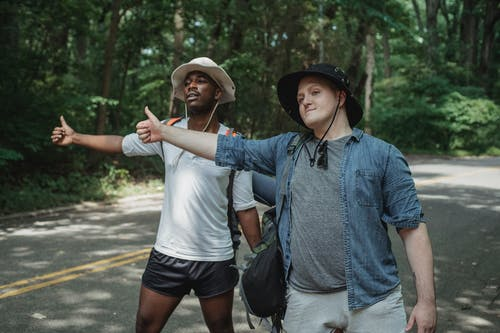 Content multiethnic male hitchhikers in casual outfits and hats with backpacks standing on roadside with thumbs up in lush forest