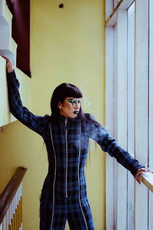 Stylish Asian woman with body art on face near window