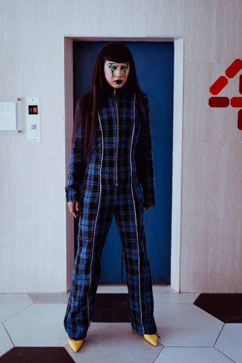 Full body of stylish Asian female with body art on face in checkered costume and shoes looking at camera while standing near doors of lift with number of floor on wall