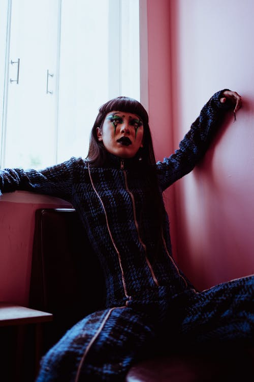 From below of Asian female with body art on face sitting near window with outstretched arms in room with pink walls