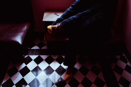 From above of crop anonymous female in trendy footwear and coat sitting on pouffe in room with checkered floor