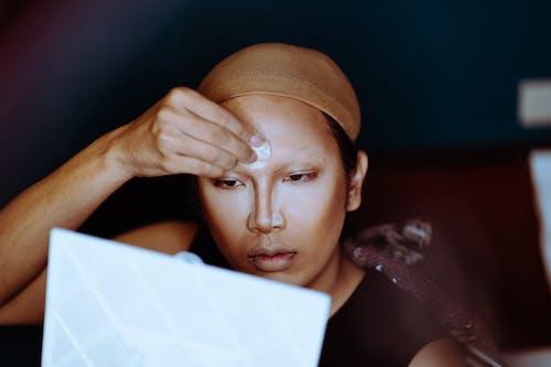 Asian woman applying makeup and looking at mirror