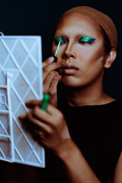 Focused ethnic female applying fluid green and blue eyeshadows while looking at mirror