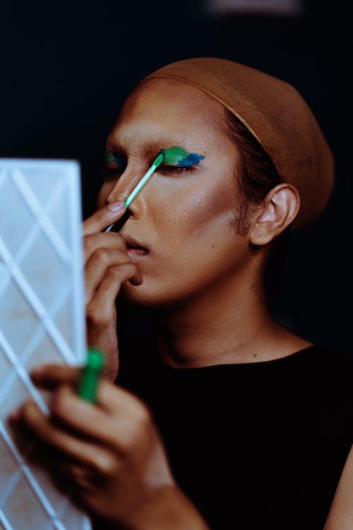 Ethnic woman applying makeup on eyelid using applicator