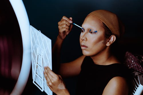 Asian woman with wig cap applying bright eyeshadows