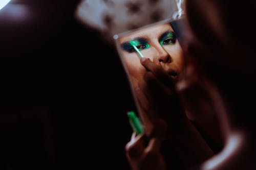 Wanita Crop Etnik Melakukan Riasan Di Kelopak Mata Yang Bercermin