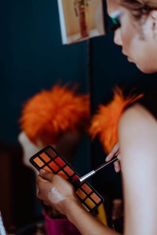 Side view of crop ethnic female artist doing make up with brush in dressing room