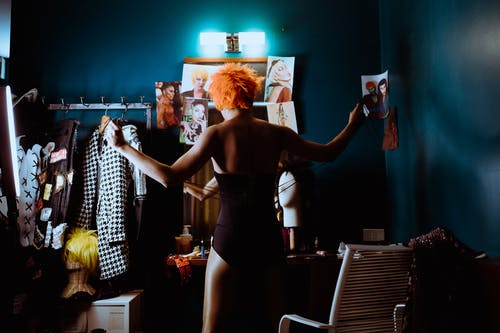 Back view of anonymous androgynous dancer in stage clothes and wig tying corset while standing near mirror in dark dressing room