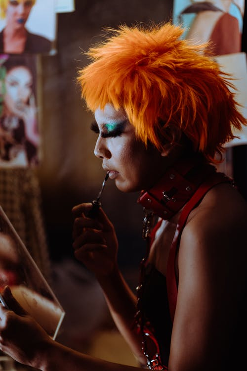 Focused ethnic transsexual artist applying makeup before show