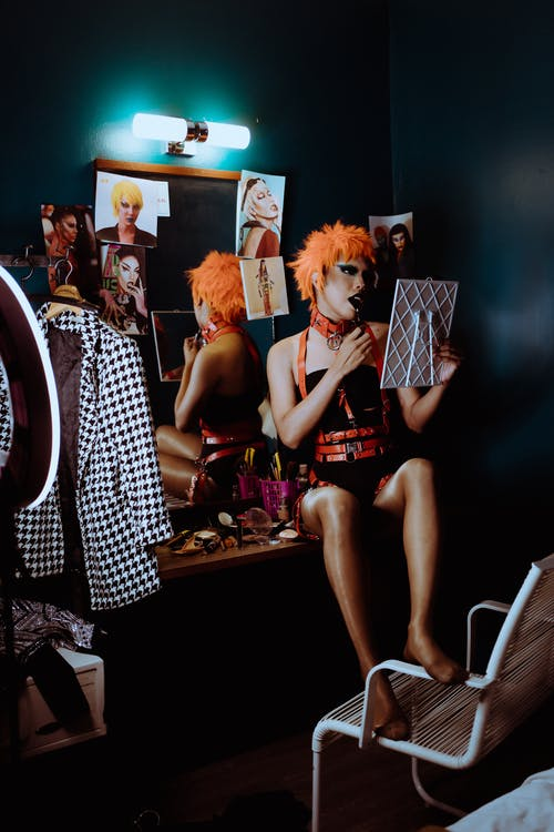 Young transgender ethnic man in stage clothes sitting on mirror table in dressing room