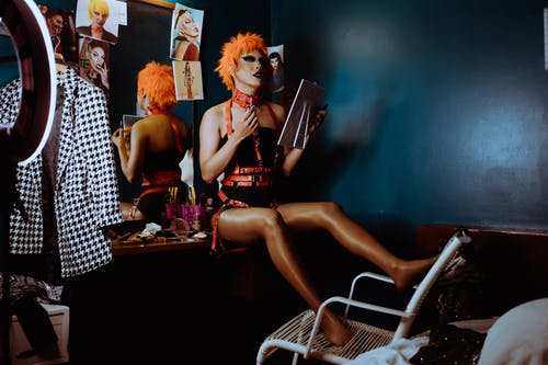 Full length of extravagant transsexual young male in BDSM harness and collar sitting on mirror table and applying makeup before show in nightclub