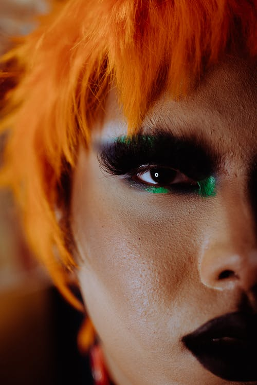Closeup of crop extravagant ethnic androgynous person with bright makeup and wig looking at camera