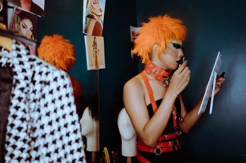 Extravagant ethnic gender fluid man in provocative clothes applying makeup in dressing room