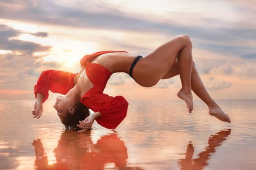 Flexible young fit woman doing gymnastics on sandy seashore at sunset