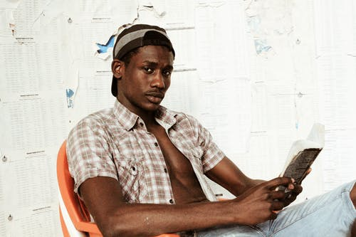 Calm African American male in hat wearing open shirt sitting on chair near wall with paper and looking at camera while reading book