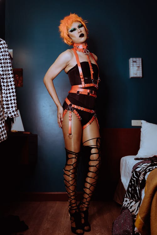 Transsexual man in BDSM outfit standing in dark room