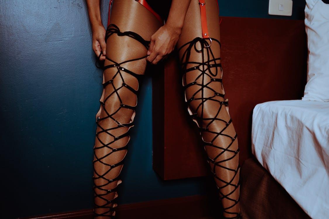 Анонимная чувственная проститутка завязывает шнурки в спальне