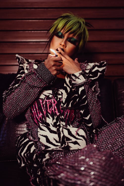 Stylish model with bright hairstyle smoking cigarette