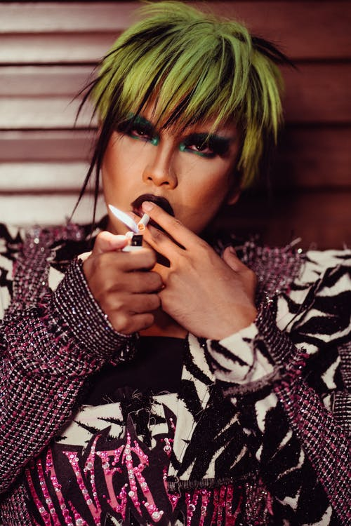 Serious male transsexual model with cool hairstyle and bright makeup smoking cigarette while looking at camera