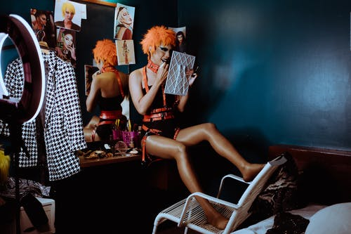 Bizarre woman applying black lipstick in dark room