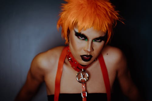 Eccentric woman with dark makeup and dyed orange hair